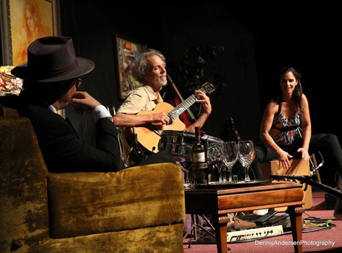 Playing at the Six String Society concert with Gregory Page listening on the couch and Monette Marino on the cajon.