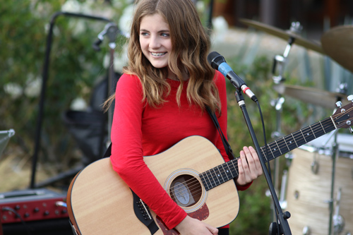 Kate Sprague playing the guitar and singing. photo by Kevin Kinnear
